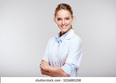 Medical concept of young beautiful female doctor in white coat, waist up. Woman in hospital looking at camera and smiling, studio, grey background