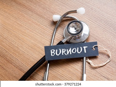 Medical Concept-Burnout word written on label tag with Stethoscope on wood background