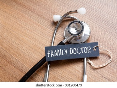 Medical Concept-Family Doctor word written on label tag with Stethoscope on wood background
