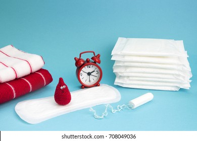 Medical conceptual photo. Red dreamy smile crochet blood drop, daily and menstrual pad and tampon. Woman critical days, gynecological menstruation cycle. Menstruation sanitary feminine hygiene