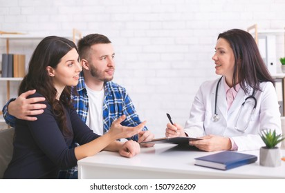 Medical consultation. Cheerful doctor talking with millennial family about health care and disease preventions, free space