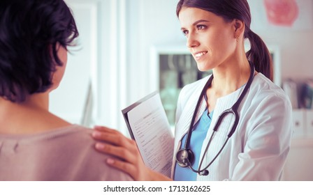 Consulta médica. Doctora sosteniendo a una paciente al hombro, calmando su miedo