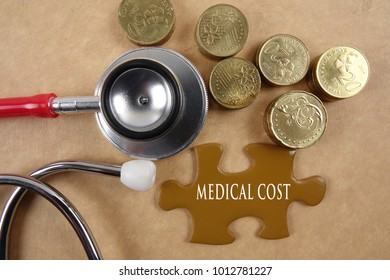 MEDICAL COST CONCEPT: Medical concept with stethoscope,piece of puzzle and coins .