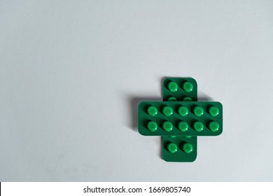 Medical cross sign made of two green blisters with pills isolated on grey background. Healthcare concept.