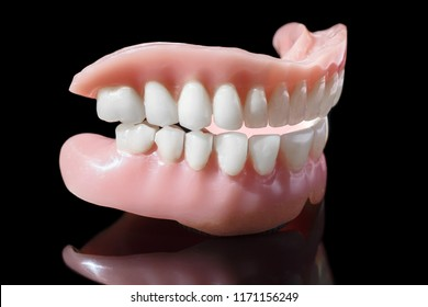 Medical denture smile jaws teeth close up isolated on black background