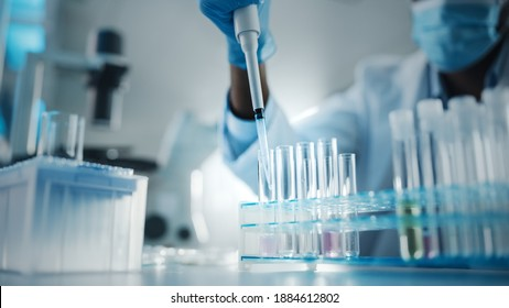 Medical Development Laboratory: Black Scientist wearing Face Mask Uses Micro Pipette, Filling Test Tube with Liquid, Conducting Experiment. Pharmaceutical Lab with Medicine, Biotechnology Researchers