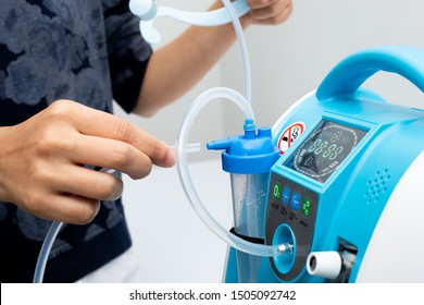 Medical Device Individual Blue White portable oxygen cylinder to put gas for patients with respiratory disorders, woman hand try to plug in the rubber tube to tank