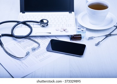 medical devices on the table at the doctor on a light background with wooden texture with blue toned