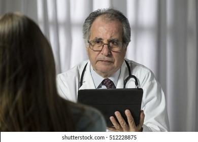 Medical doctor consulting with his patient and using a computer tablet