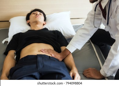 Medical doctor hand touching young Asian sick patient at stomach to investigate or inspect  abdomen pain. Healthcare of diarrhea from Rotavirus.