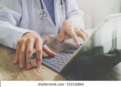 medical doctor hand working with smart phone,digital tablet computer,stethoscope eyeglass,on wood desk,filter effect