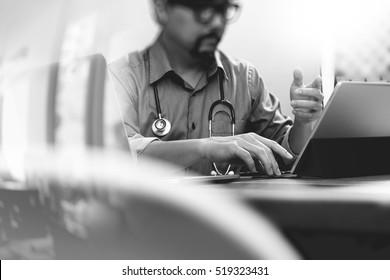 medical doctor hand working with smart phone,digital tablet computer,stethoscope eyeglass,on wood desk,black white