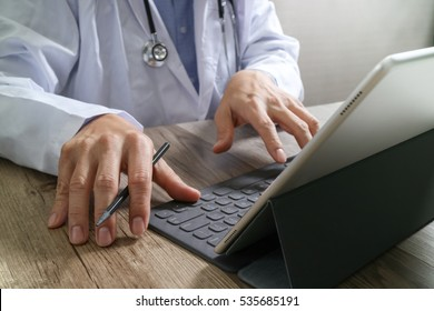 the medical doctor hand working with smart phone,digital tablet computer,stethoscope eyeglass,on wood desk