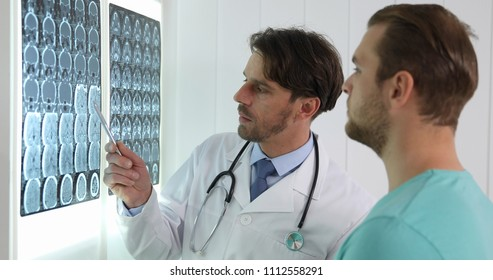 Medical Doctor Man Having a Dialogue with Young Patient About his Brain Mri Results in Hospital Cabinet or Healthcare Center Room