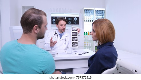 Medical Doctor Man Talking with Young Married Couple About Ultrasound Diagnostic Result, Pregnant Woman Visit Hospital for Check Up Monthly Control