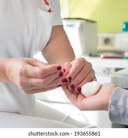 Medical doctor performing a quick prick test for blood group determination by using blood type testing kit with anti A and B antibodies on a white card.
