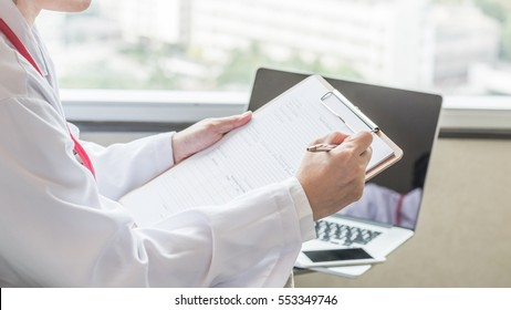 Medical doctor or physician with personal patient's health record pad in hospital or clinic