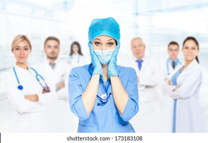Medical doctor serious team negative emotions problem, woman with stethoscope hold hand head stress, nurse wear blue surgery suit gloves mask cap in hospital over people group background