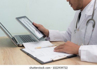 Medical doctor shows image patient x-ray of the lungs with his digital tablet, smoking cigarettes problem