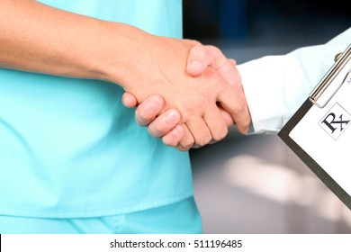 medical doctor  with a stethoscope around his neck shaking hand with colleague