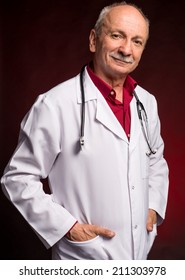 Medical doctor with stethoscope on a dark red background
