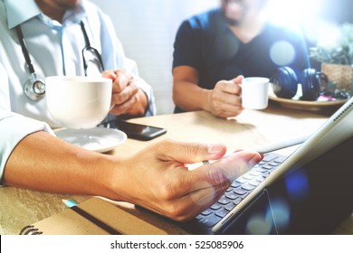 Medical doctor team taking coffee break.using digital tablet docking keyboard and smart phone on marble desk.listen music,filter film effect