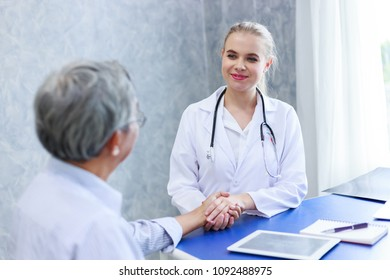 medical doctor woman holding senior patient's hands and comforting him