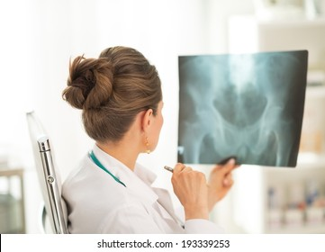 Medical doctor woman looking on fluorography. rear view
