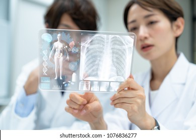 Medical doctors looking a futuristic tablet device. Electronic medical records.