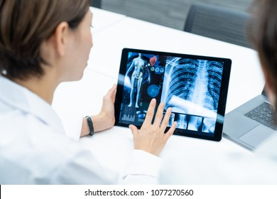 Medical doctors looking at a screen of tablet PC. Medical technology concept.
