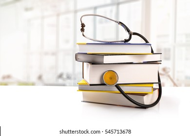 medical education - stack of books with stethoscope on the table in library