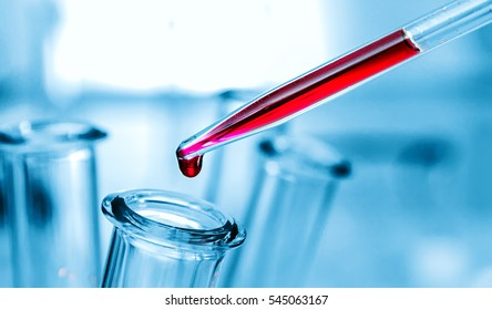 Medical equipment. Blood test.Pipette adding fluid to one of several test tubes .