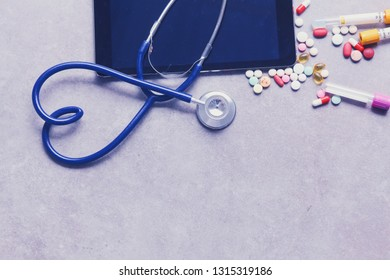 Medical equipment: blue stethoscope and tablet on gray background.