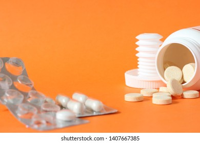 Medical equipment. Close up photo of tablet, pills, drops and other drugs isolated on orange background, studio shot, macro photography. Concept of standard medical treatment of sickness with drugs.