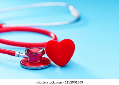 Medical equipment: red stethoscope on blue background.
