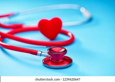 Medical equipment: red stethoscope or phonendoscope on blue background.