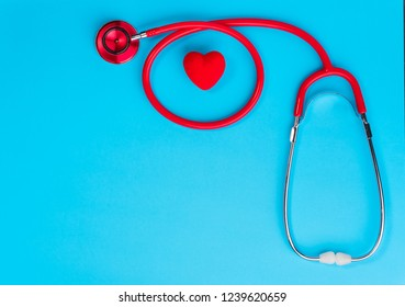 Medical equipment: red stethoscope or phonendoscope on blue background.World health day.Medicine concept.