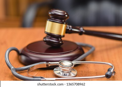 Medical error and trial. Forensic Medicine. Trial of doctor. Judge's gavel, doctor's statoscope on the table in the courtroom.