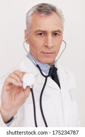 Medical exam. Senior grey hair doctor in uniform looking at camera and holding his stethoscope outstretched while standing isolated on white