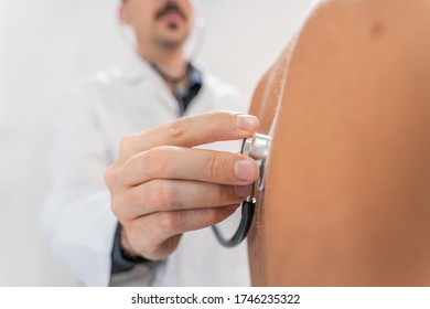 Medical examination with stethoscope. Medical examination on patient back in clinic. Traumatology. Hospital. Injured. Therapy. Care.