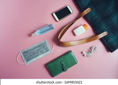 Medical face mask, alcohol spray bottle, alcohol-based hand sanitizer gel, tote bag, purse, smartphone, earphone on pink background. Essential items people need to survive in the COVID-19 epidemic.