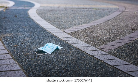Medical face mask fall to the ground in street. Lost disposable face mask for protection the coronavirus Covid19. Improperly discarding the used masks haphazardly strewn on pavement