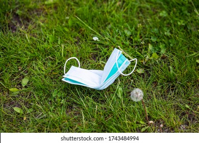 Medical Face Mask On The Ground. Used Surgical Mask Haphazardly Thrown On Pavement. Improperly Discarding Used Face Mask. Lost Face Mask On The Grass.