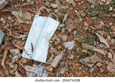Medical Face Mask On The Ground, Used Surgical Mask Haphazardly Thrown On Pavement. Improperly Discarding Used Face Mask, Lost Face Mask On The Grass.