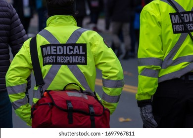 Medical first responders walking along a road wearing black wool stocking caps, yellow reflective coats with the medical first responder in grey letters and across. The EMT is carrying a first aid kit