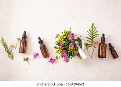 medical flowers herbs in mortar essential oils in bottles. alternative medicine. clover milfoil tansy rosebay