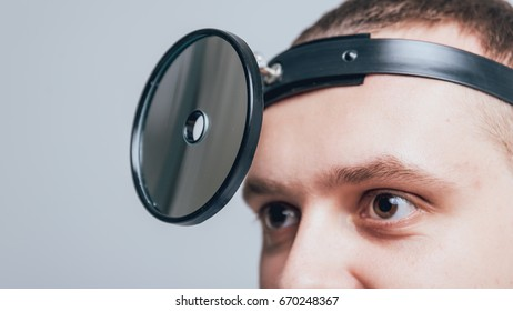 Medical frontal reflector on the doctor's head. Background