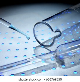 Medical glass test tube and dropper on light blue color background in steel