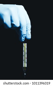 Medical glass thermometer in hand on black background