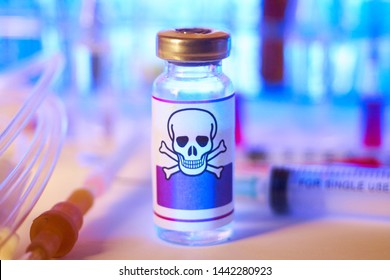 Medical glassware with the poison label sign. Container with a poison, warning label with a skull and bones. Selective focus